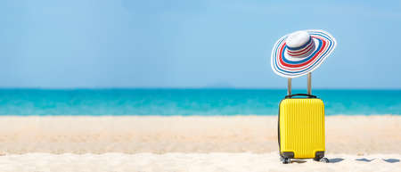 Summer traveling and tourism planning with yellow suitcase luggage with big hat fashion in the sand beach. Travel in the holiday, blue sky and beach background. Summer and Travel Concept, copy space for banner Stok Fotoğraf