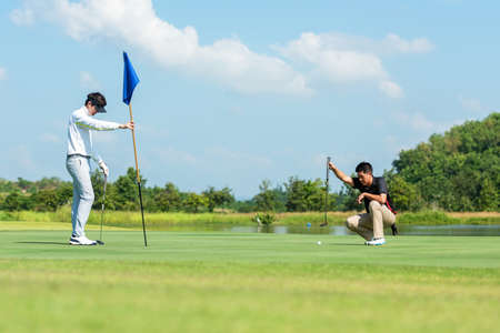 Golfer man and friend playing golf aiming shot for putting ball on the hole with club on green course.  Professional people hobby in holiday and vacations in sunny morning day on club golf. Lifestyle and Sport Concept Stok Fotoğraf