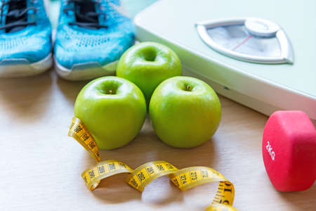 Healthy lifestyle for women diet with sport equipment, sneakers, measuring tape, vegetable fresh, green apples and bottle of water on wooden.  Healthy Concept. Stok Fotoğraf