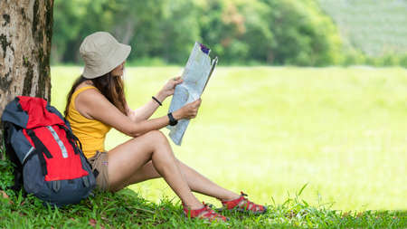 Asian women hiker or traveler with backpack adventure holding map to find directions and sitting relax in the jungle forest outdoor for education nature on vacation. Travel and Lifestyle Concept