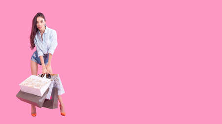 Asian smiling woman so happy with her shopping in casual clothing with shopping bags on the wall pink background, Lifestyle Concept.