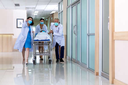 Team medical doctor pushing stretcher gurney bed corridor with female patient in hospital. Health care Concept Foto de archivo