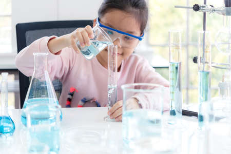 select focus. Asian children analyzing study evaluating microscope with scientist. Health care researchers doing some research with dropper chemical testing and working in life science laboratory
