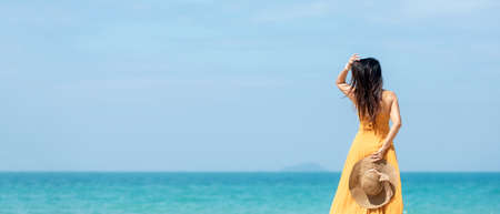 Summer vacations. Lifestyle woman relax and chill on beach background.  Asia happy young people wearing yellow dress fashion summer trips walking enjoy  tropical beach. Lifestyle and Travel Concept.