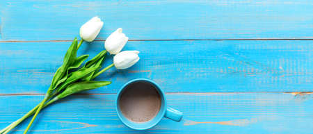 Cozy winter relax time.  Cup of hot coffee with tulip flower on the blue wood background in morning sunny day. Lifestyle concept.  copy space and banner for text Stok Fotoğraf