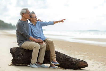 Asian Lifestyle senior couple pointing and hug see beach happy in love romantic and relax time.  Tourism elderly retirement family travel leisure destination and activity after retirement in vacations and summer.