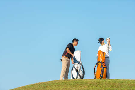Group golfer asian two man approach on the tee off for swing and hitting golf ball and looking fairway in course. Hobby in holiday and vacations in sunny morning day on club golf. Lifestyle, and sport Concept.