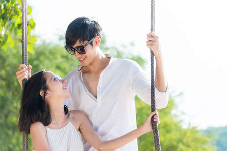 Smiling lifestyle asia couples lover and happy on the hammock. people woman and man relax and romantic honeymoon in luxury resort near the beach. Summer Travel Concept. Archivio Fotografico