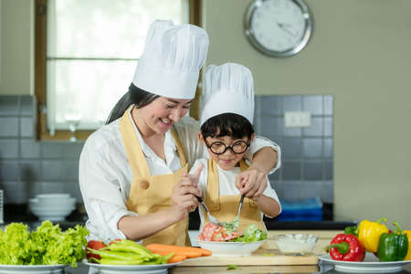 Cooking Family. Chef kid boy and mother making and leaning fresh vegetables salad for healthy eat and education.  Asian son helping make food, so happy and enjoy.  Family Lifestyle Concept