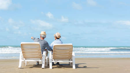 Asian Lifestyle senior couple hug and pointing on the beach happy in love romantic and relax time. People tourism elderly family travel leisure and activity after retirement in vacations and summer.