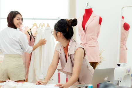 select focus. Asian young women fashion designer working and taking with customer in the showroom. Lifestyle Stylish tailor taking measurements on mannequin in studio. Business small Concept