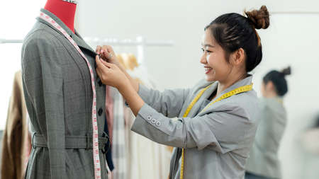 Work from home. Asian young woman fashion designer working on her design in the showroom. Lifestyle people Stylish tailor taking measurements on mannequin in studio. Business small Concept