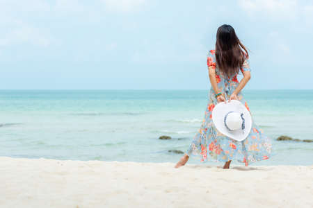 Summer Trips.  Lifestyle woman wearing fashion summer walking and holding big hat on the sandy ocean beach. Happy people truist travel enjoy and relax vacation.  Lifestyle and Travel Summer Concept. Banco de Imagens