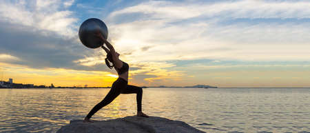Silhouette healthy woman yoga ball balance body exercising vital meditate and practicing on the rock outdoor in the beach at sunset. Healthy and Lifestyle Concept. copy space for banner Banco de Imagens