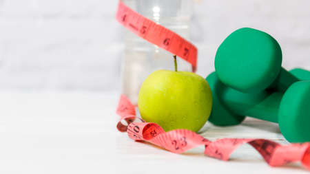 Close up green apple with measuring tape.  Diet Health Plan.  Nutrition start up workout planing. Sport exercise equipment workout gym background. Healthy Lifestyle Concept