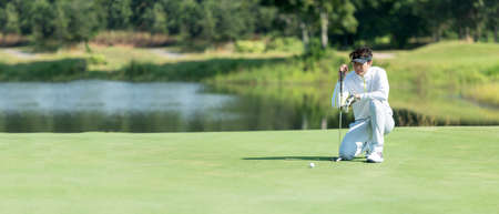 Golfer man playing golf aiming shot for putting ball on the hole with club on green course.  Professional people hobby in holiday and vacations in sunny morning day on club golf. Lifestyle and Sport Concept, copy space for banner