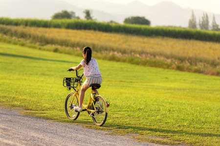 Family Happy.  Asia gird happy and relax outdoor with bicycling at the garden meadow in sunset.  Lifestyle Family Concept