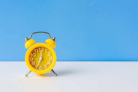 Alarm yellow vintage alarm clock falling on the floor with blue color background, copy space for tex.  Morning and Start up Concept
