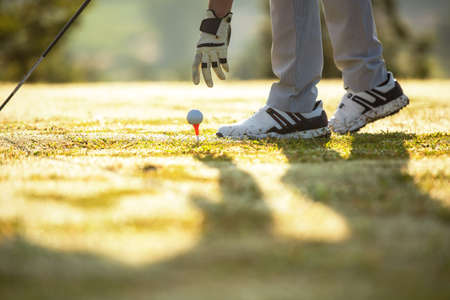 Close up hand putting golf ball on the green before golfer  lifestyle man approach playing game golf tee of.  people  sport man in course golf fairway  player game shot in summer. Healthy and Sport outdoor Banco de Imagens