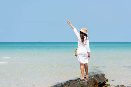 Summer vacations. Lifestyle woman relax and chill on beach background.  Asia happy young people with white dress raise arm on the wave sea, summer trips walking enjoy  tropical beach. Lifestyle and Travel Concept Banco de Imagens