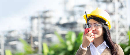 Engineers woman holding radio, blueprint and report schedule for workers security control at power plant energy industry. Engineer and industryConcept,  copy space for banner