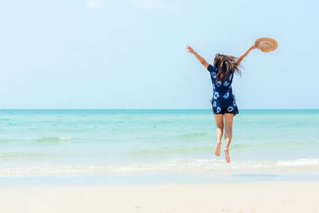 Summer vacations. Lifestyle woman relax and chill on beach background.  Asia happy young people jumping on the wave sea, summer trips walking enjoy  tropical beach. Lifestyle and Travel Concept. Banco de Imagens