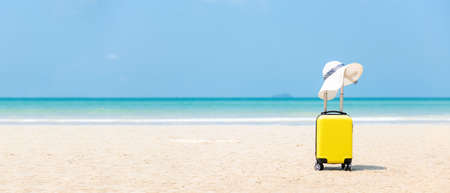 Summer traveling and tourism planning with yellow suitcase luggage with big hat fashion in the sand beach. Travel in the holiday, blue sky and beach background. Summer and Travel Concept, copy space for banner Banco de Imagens