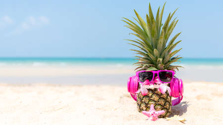 Summer in the party.  Hipster Pineapple Fashion in sunglass and listen music on the sand beach beautiful blue sky background.  Creative art fruit for tropical style.   Fashion Summer Vacation Concept