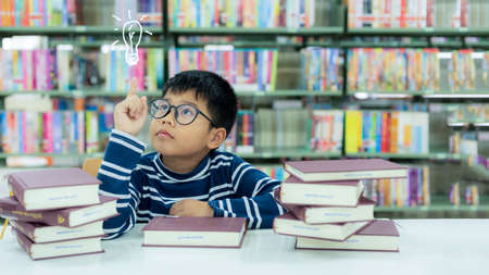 Asia schoolboy thinking good idea after reading books for education and go to school in library. Education and Lifestyle Concept