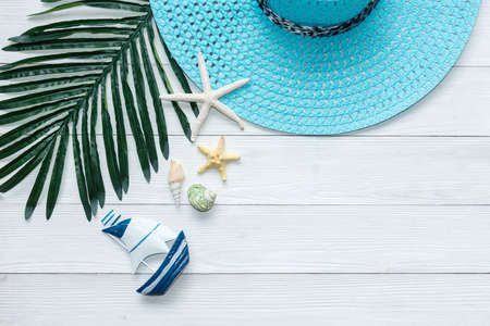 Summer Fashion tourism woman big hat and accessories to travel in the beach. Tropical sea. Unusual top view, wood white background. Summer and Trips Concept.