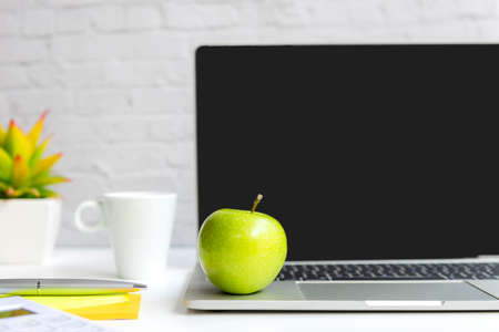 Healthy snack with working in office.  Green apple with laptop on white dress working.  Healthy Lifestyle Concept