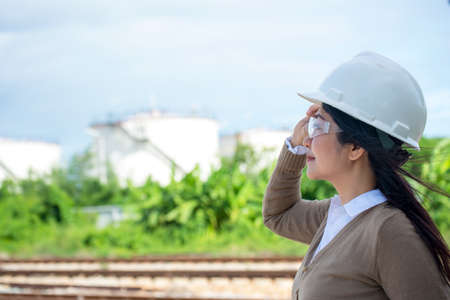 Engineers woman holding blueprint and report schedule for workers security control at power plant energy industry. Engineer and industry Concept