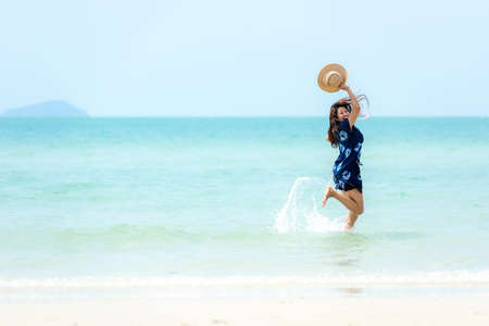 Summer vacations. Lifestyle woman relax and chill on beach background.  Asia happy young people running on the wave sea, summer trips walking enjoy  tropical beach. Lifestyle and Travel Concept. Banco de Imagens