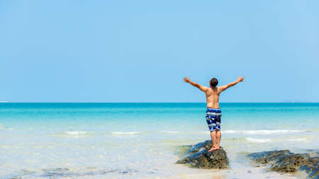 Summer vacations. Lifestyle man raise arm relax and chill on the rock, blue beach and sky background.  Asia happy young people standing near the wave sea, summer trips enjoy tropical beach. Lifestyle and Travel Concept.  Copy space for banner Banco de Imagens