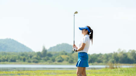 Golfer women sport course golf ball fairway. People lifestyle woman playing game golf tee of on the green grass sunset background. Asia female player game shot in summer. copy space banner