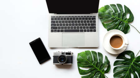 Traveler planning vacation trip and searching tourist attraction and information or booking hotel on laptop with accessories item women and map, old camera.  Top view and  leaf green background.  Travel concept