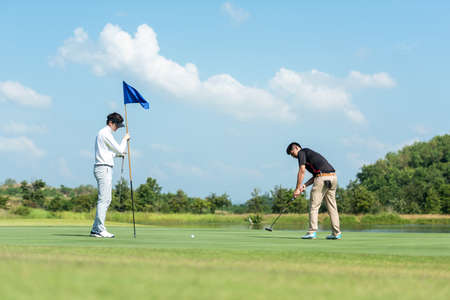 Golfer man and friend playing golf aiming shot for putting ball on the hole with club on green course.  Professional people hobby in holiday and vacations in sunny morning day on club golf. Lifestyle and Sport Concept Banco de Imagens