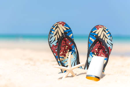 Protective sunscreen or sunblock and sunbath lotion for healthy care skin woman in white plastic bottles with sandal, starfish on sand tropical beach, summer accessories in holiday.  Summer Concept Banco de Imagens