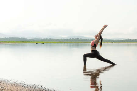 Yoga women lifestyle exercise and pose for healthy life. Young girl or people pose balance body vital zen and meditation for workout sunrise morning reflection on the water nature background. Health care Concept
