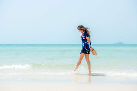Summer vacations. Lifestyle woman relax and chill on beach background.  Asia happy young people walking on the wave sea, summer trips enjoy  tropical beach. Lifestyle and Travel Concept.