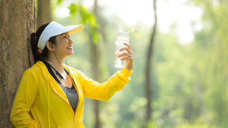 Healthy athletic asia woman is drinking pure water from the bottle refreshing herself after exercise in the nature park. Healthy and Lifestyle Concept
