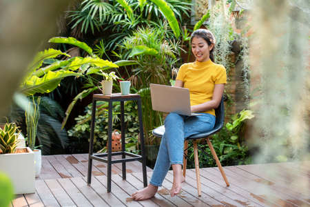 Young people work from home with laptop and drinking coffee in garden nature at home. Asia woman meeting conference connect online with office.  Business and Technology Concept Фото со стока