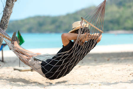Lifestyle freelance man relax and sleeping on the hammock after using laptop working and relax on the beach. Asia people success and together your work pastime and meeting conference on internet in holiday. Business and Summer Concept
