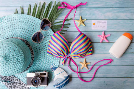 Summer items fashion tourism woman swimsuit Bikini with sunblock and big hat. Traveler tour pay credit card for travel and vacations trip in the holiday on blue wood background, top view. Summer and Travel Concept.