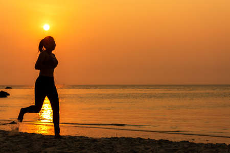 Silhouette athletic woman jogging and relax and freedom on sand beach. People running and workout in sunset background. Lifestyle and Healthy Concept.