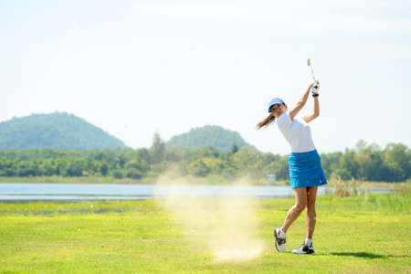 Golfer sport course golf ball fairway. People lifestyle woman playing game golf and hitting out of sand trap go on green grass. Asia female player game shot in summer. Healthy and Sport outdoor