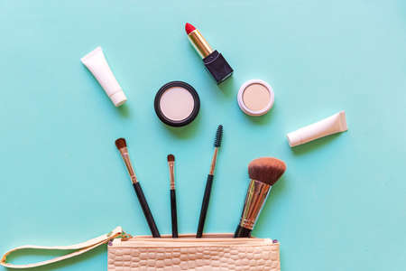 Makeup cosmetics tools background and beauty cosmetics, products and facial cosmetics package lipstick, eye shadow on the blue background. Lifestyle Fashion Concept Фото со стока
