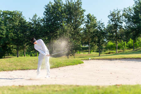 Asia Golfer man hitting out of a sand trap. The golf course is on the sand.  Hobby in holiday and vacations on club golf. Lifestyle and Sport Concept