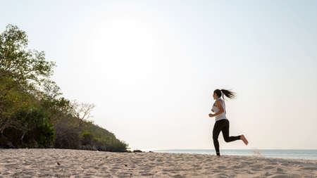Athletic woman jogging and relax and freedom on sand beach. People running and workout in sunset background. Lifestyle and Healthy Concept.
