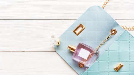 Fashion blue bag woman accessories set. Trendy blue fashion with perfume on wood white background. Fashion Concept.